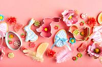 Easter frosted cookies in shape of egg chicken and rabbit, sugar sprinkles, candies, cookie cutters on pink background. Flat lay mockup.