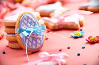 Easter baking background of frosted cookies in shape of egg on pink background.