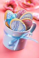 Easter baking background of frosted cookies in shape of egg in blue mug on pink background.