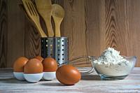 Eggs and flour with bakery utensils.