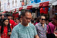 . Singapore, Republic of Singapore, Asia - Crowds of people at a busy street bazaar in Chinatown that takes place every year around the time of Chines...