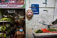 Singapore, Republic of Singapore, Asia - A woman wearing a protective corona face mask in front of a grocery store in the city district of Little Indi...