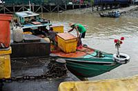 Yangon, Myanmar, Asia - Workers unload cooling boxes from a boat at the traditional Baho San Pya Fish Market, a wholesale market in the commercial cap...