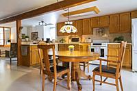 Red pine wood claw foot dining table with red oak wood and black leather seat high back chairs in kitchen with oak wood cabinets and white ivory linol...