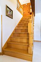Varnished natural oak wood staircase leading to upper floor inside an old 1807 river and fieldstone cottage style house, Quebec, Canada.
