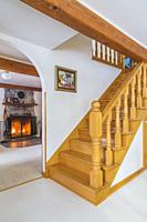 Varnished natural oak wood staircase leading to upper floor plus lit fireplace with fieldstone mantle-piece and firewood storage box in living room wi...