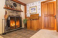 Lit fireplace with fieldstone mantle-piece and firewood storage box in living room with beige carpeting and ceramic tile floor inside an old 1807 cott...
