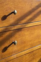 Close-up of brass metal knobs on drawers of maple wood dresser in guest bedroom inside an old 1807 cottage style house, Quebec, Canada.