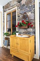 Wooden cabinet against original river and fieldstone wall decorated with red silk geranium flowers, antique washboard and window in extension with flo...