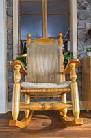 Canadiana style pine wood rocking chair with large turned posts against original stone wall with window in extension with floating wood floor at back ...