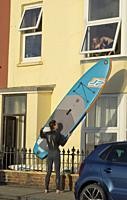 Young people with surfing board at the South Beach promenade, Aberystwyth,Ceredigion,Wales,UK.