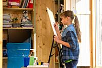 A ten-year-old girl draws on an easel at home.
