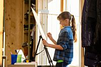 A ten-year-old girl makes a sketch on an easel, removes unnecessary details with a washing eraser.