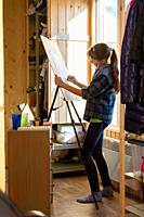 A ten-year-old girl draws with paints on an easel at home.