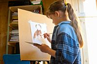 A ten-year-old girl draws with paints on an easel.