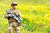 Equipped and armed special forces soldier in the blooming field with copy space for text.