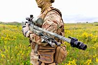 Soldier with sniper rifle standing in blooming green field.
