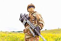 Armed special forces soldier with sniper rifle stands in field.