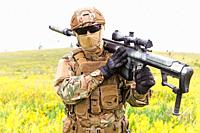 Special forces soldier walks across the yellow field with sniper rifle close up.