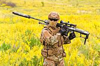 Soldier with big sniper rifle walks across blooming field.