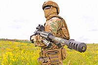 Special forces soldier standing in the green field with sniper rifle.