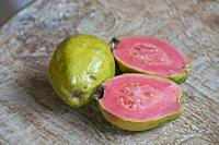 Fresh pink goiaba on wooden table.