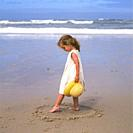 Little three-year-old girl with hat in hand and foot playing in the sand on the beach on a sunny day by the sea.