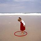 Little three-year-old girl with a red hula hoop playing in the sand on the beach on a sunny day by the sea.