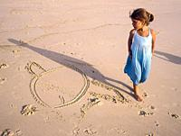Six-year-old girl in a blue dress and a drawing of a fish in the sand on the beach one summer afternoon.