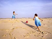 Two girls aged six and eleven in blue dresses playing with a red ball on the beach one summer afternoon.