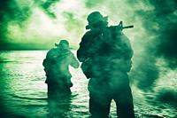 Commando soldiers walking in water, army special operations forces fighters sneaking in darkness, aiming assault rifles and observing shore during amp...