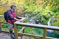 Hiker man in a viewpoint close to a river. Urederra river source. Urbasa-Andia Natural Park. Navarre, Spain, Europe.