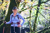 Hiker woman with a walking stick in a beechwood. Urbasa-Andia Natural Park. Navarre, Spain, Europe.