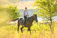 A girl rides a horse on a warm autumn day.