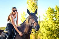 Girl with glasses strokes a horse on a horse ride.