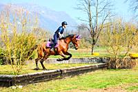 Italian horsewoman in country riding shows trim and balance rider and horse.