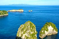 Indonesia. A few rocky islets with jungle. Mountains and clouds on the horizon.