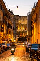Roman street with the colosseum in the background at night in Rome, Italy i