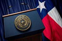 Press conference of governor of the state of Texas concept. Big Seal of the State of Texas on the tribune with flag of USA and Texas state. 3d illustr...