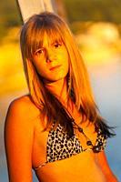 Teen girl is alone sad wearing bikini swimsuit bra lit by warm sunset light
