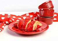 baked croissant with cherry glaze on a red ceramic plate, white table, close up.