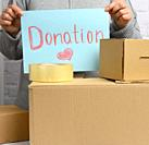 a woman in a gray sweater holds a blue sheet of paper with the inscription donation, help and volunteering concept.