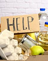 cardboard box with various products, fruits, pasta, sunflower oil in a plastic bottle and preservation. Donation concept.