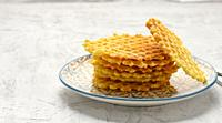 stack of baked Belgian waffles on a round plate on a white table, delicious breakfast, close up.