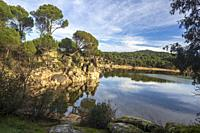 Pines, hills, rocks, clouds and reflections at St. John reservoir. Madrid. Spain. Europe.