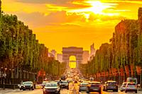 France. Summer evening in Paris. Traffic on the Champs-Elysees and the Arc de Triomphe. Golden sunset.