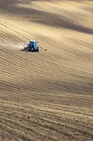 Tractor with seed drill in early spring landscape.