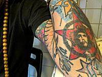 Tilburg, Netherlands. Tattoot arm of a Multi Artist and Tattoist, sitting on his kitchen table.