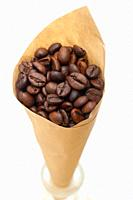 espresso coffee beans on a paper cone cornucopia over white background.