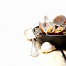fresh clams stewed on an iron skillet over wite rustic wood table.